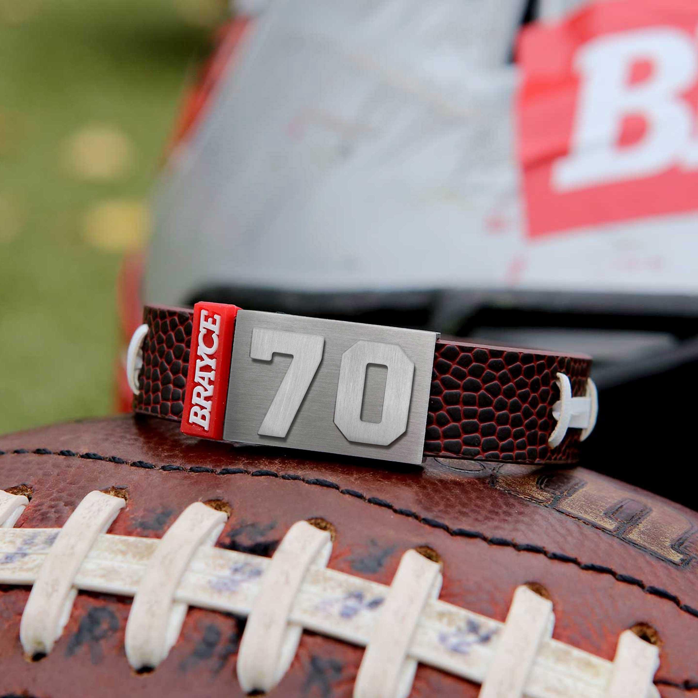 American Football Armband mit Trikotnummer 70 auf einem Football liegend